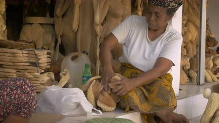orgulho : An elderly Balinese woman sanding a hand made sculpture made of wood in her work shop