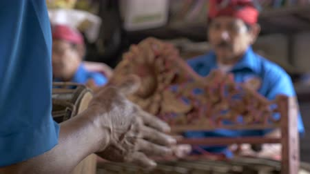 akılsız : Close up of a hand playing a hand drum with two other musicians in the background at a Hindu ceremony.