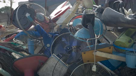 wasteful : A large pile of broken electric fans outside a recycling center Stock Footage