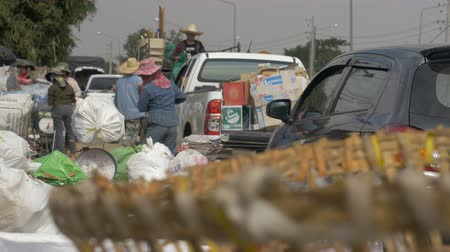 wasteful : Hand held shot from behind bags of recycling as people unload a pick up truck with more and more garbage Stock Footage