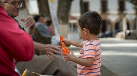 nagyapa : PATZCUARO, MEXICO - CIRCA AUGUST 2016 - an elder helps a young boy blow up a balloon in slow motion while he shows excitement.