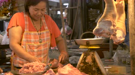gruesome : A happy Asian woman weighs animal organs in a rusty scale in a traditional market as she slices pieces of the unknown meat Stock Footage