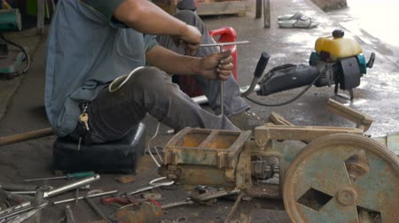 substituição : An asian man replaces the starter cord of a weed wacker with hand tools in his busy machine and repair shop