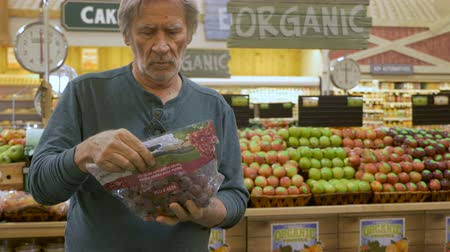 дата : An elderly senior man picks out grapes while shopping in a modern generic supermarket with signs of organic produce in the background
