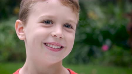 suçsuzluk : Close up portrait of an adorable young 4 or 5 year old boy smiling outside during the day - room for text Stok Video