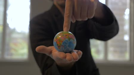mapa : Push in of a man in a business sports coat with the world in his hands
