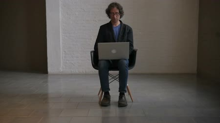 steril : Pushout revealing a man in a sports coat and glasses working on his laptop computer in an empty room Stok Video