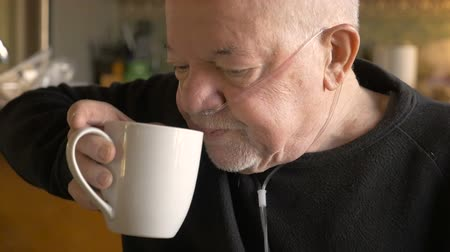 sıkıntı : A senior man drinking coffee while wearing oxygen supplementation in slowmo