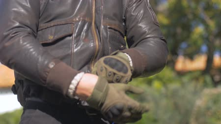 motorkerékpár : A caucasian man puts his bare hand into a motorcycle riding glove with his other hand that is already wearing a glove