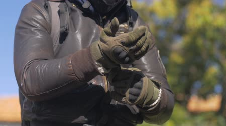 motor vehicle : A man in a brown leather jacket securing his motorcycle riding gloves with the strap around his wrist outside. Stock Footage