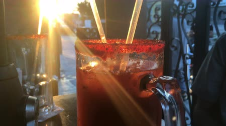 szalma : Close up of a michelada or bloody mary cocktail at an outdoor cafe - hand held Stock mozgókép