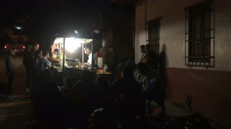 hladový : PATZCUARO , MEXICO - CIRCA JULY 2016 - People gather around a taco stand at night to eat dinner.