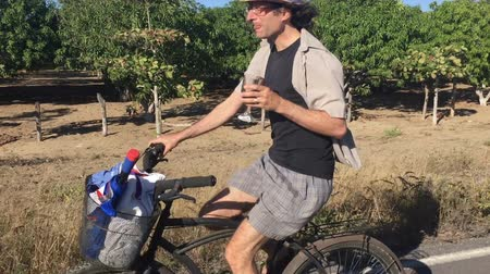 na zdraví : A man in his early 30s cheers the camera while riding a beach cruiser bike on an empty paved road while drinking wine. Dostupné videozáznamy
