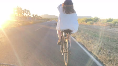 an : The camera follows a woman with blond hair riding a bicycle into the sun on a paved road with an approaching car