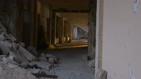 ürpertici : An abandoned hallway with crumbling bricks and debris in a hotel damaged during a major earthquake with erie sunlight shining in - dolly shot Stok Video