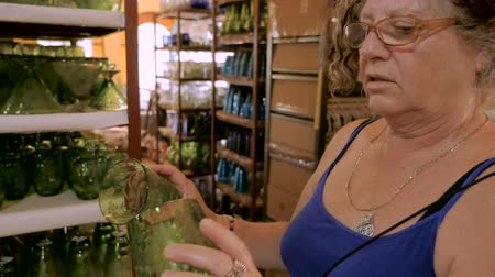 suvenýry : A woman in her early 60s comparing two green glasses while shopping in slow motion