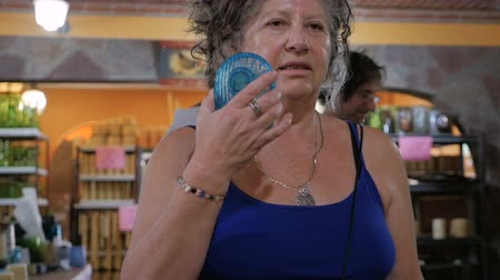 nedvesség : A older woman cools herself off with a portable fan in the summer while two people shop in the background in slow motion