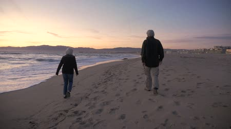matky : The camera follows an attractive senior couple wearing jackets walking on the beach at dusk in slow motion