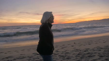 nagymama : Happy healthy attractive fit mature active retired 60s woman looking at beach sunset in slow motion.