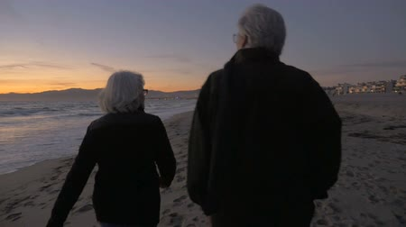 Mature fit active retired 60s couple walking on beach during sunset or sunrise from behind in slow motion Stok Video