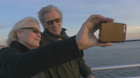 fotky : Attractive happy elderly couple in 60s take selfie with smartphone technology at sunset on ocean smiling and laughing together. Retired baby boomers using cell phone for photos and sharing on social media apps
