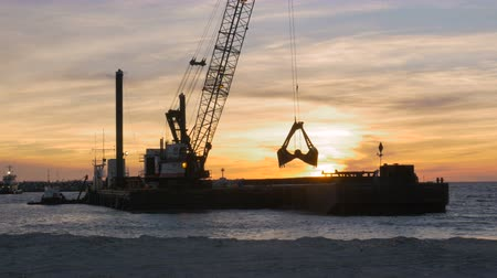 sosyal konular : Dredger ship removing sand from ocean bottom at sunset to control beach erosion from climate change