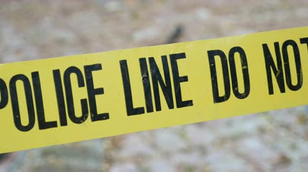 investigar : Exterior crime scene tape outside daytime Police Line Do Not Cross dolly shot