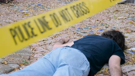 investigar : A dead murdered killed man roped off with Police Line Do Not Cross tape at crime scene - dolly shot