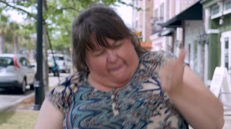 жир : Full figured beautiful woman silly dancing celebrating achievement and success in urban city streets during day