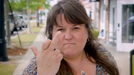 mračící : Very pissed off heavy woman gives the middle finger to the camera clearly expressing her emotions outside on city sidewalk during day