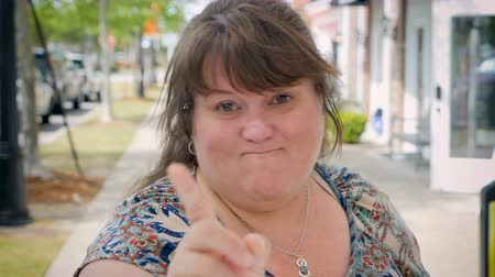 mračící : Angry attractive curvy woman waves her finger expressing no way to the camera outside on city sidewalk during day
