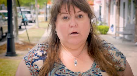 mračící : A frightened scared natural plus size woman showing fear while standing outside an outdoor shopping mall.