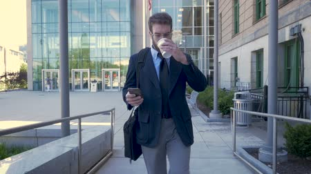 ambição : Ambitious executive millennial businessman with beard, briefcase, and to go coffee cup walking away from modern glass building and browsing on smartphone technology app in slow motion stabilized shot Vídeos