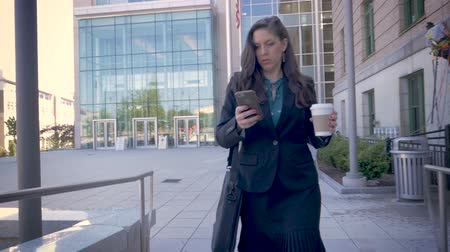 executivo : A successful millennial businesswoman executive walking away from a modern office building using smartphone technology app drinking togo coffee slow motion stabilized shot Stock Footage