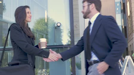 честолюбие : Two attractive millennial ambitious businesspeople shaking hands outside a modern office building in slow motion stabilized shot