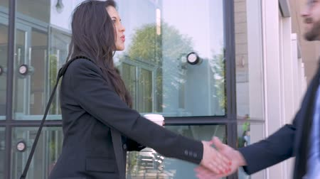 честолюбие : Two professional attractive millennial executive business people shaking hands and making eye contact outside a modern glass office building in slow motion stabilized shot Стоковые видеозаписи