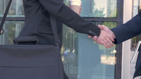 parceiro : Close up of a businessman and businesswoman shaking hands outside a modern office building in slow motion.
