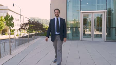 hrdý : Happy handsome successful businessman walking and smiling towards the camera in slow motion outside a modern generic office building