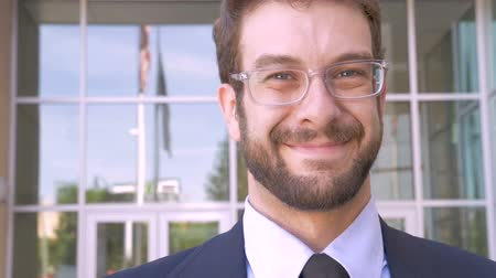 executivo : Stylish fashionable handsome happy millennial man with beard and clear eyeglasses portrait smiling with American flag reflected in glass of modern building in slow motion close up shot Stock Footage