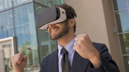 ciberespaço : Man in suit wearing VR goggles celebrating victory in an augmented virtual reality world while camera circles him in slow motion dutch angle Vídeos