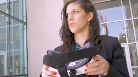ona : An unhappy professional woman holding VR headset disappointed in the real world preferring the virtual reality world she just left in slow motion low angle