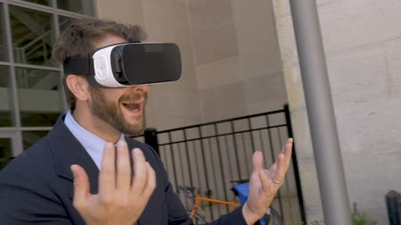 ciberespaço : Camera circles a happy smiling handsome businessman wearing a VR headset virtual reality working outside in an augmented reality in slow motion stabilized shot
