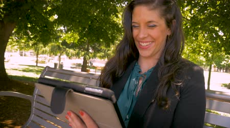 touchpad : A successful corporate millennial woman in her 30s finishing a task on her digital tablet technology smiling crane up slow motion shot
