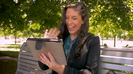 executivo : Happy attractive female corporate executive businesswoman traveler video chatting with her friends or family while away on business on her digital tablet in slow motion