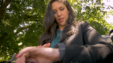ajustando : Beautiful successful businesswoman adjusting her smart watch settings in park low angle slow motion Stock Footage