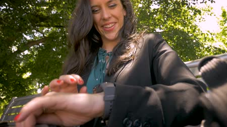 ajustando : Smiling happy woman in her 30s using smart watch app technology in park slow motion low angle
