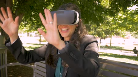 valóság : Smiling happy millennial woman using VR headset virtual reality immersion reaching and touching digital augmentation reality outside sitting on a park in slow motion handheld