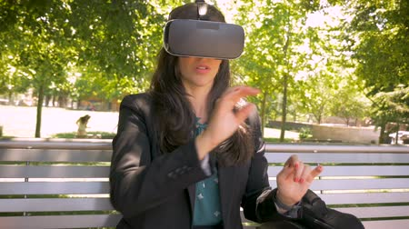 fejhallgató : Virtual reality working millennial businesswoman in her 30s wearing VR headset technology sitting outside on park bench in slow motion hand held Stock mozgókép