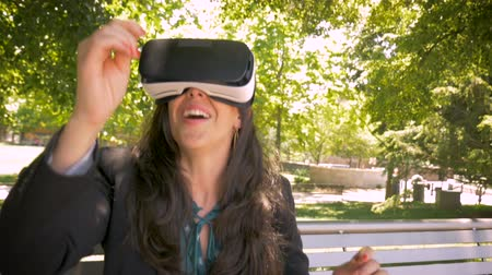 valóság : Attractive millennial female office worker in her 30s experiencing augmented 360 virtual reality with VR headset technology outside sitting on park hand held stabilized slow motion