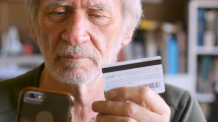 purchasing : Candid moment of a smiling happy handsome mature man in 60s or 70s checking out his purchase on smart phone with debit or credit card - dolly shot